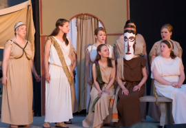 Andrea Braddy (masked) and ensemble members in Electra